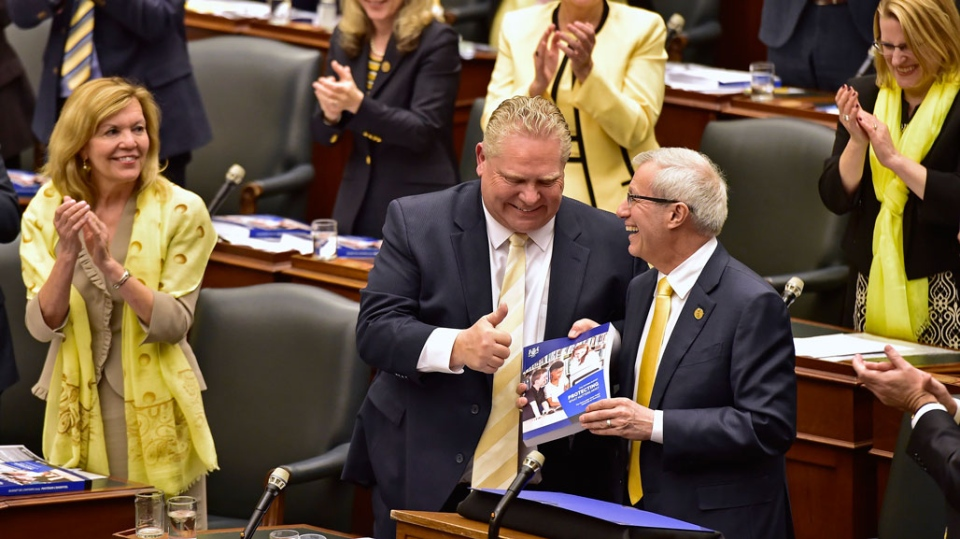 Ontario Finance Minister Vic Fedeli is applauded by Premier Doug Ford and other MPPs after presenting the 2019 budget at the legislature in Toronto on Thursday, April 11, 2019. (THE CANADIAN PRESS/Frank Gunn)