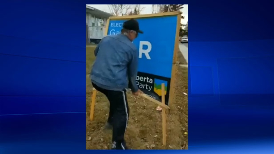 A homeowner damages a Gar Gar sign on his property in Calgary-East that his tenant had agreed to display (image courtesy: Gar Gar)