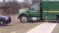 A dump truck parked across a sidewalk