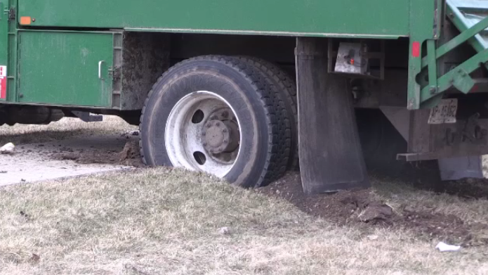 The dump truck's rear wheels dug into the ground.