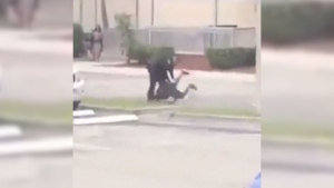 An unidentified Florida deputy takes down a Grade 6 student in an image taken from a viral video.