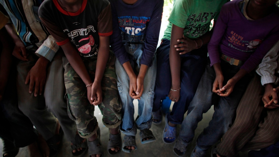 Nepalese children rescued by police during a raid on embroidery factories sit in a police station in Katmandu, Nepal,Thursday, June 13, 2013. (AP Photo/Niranjan Shrestha)