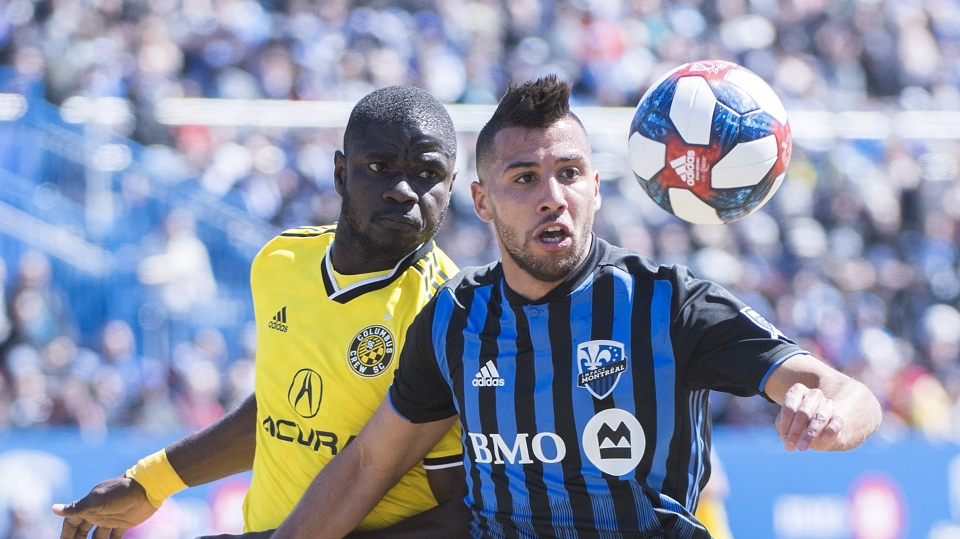 Montreal Impact's Saphir Taider, right, and Columbus Crew SC's Jonathan Mensah keep thier eyes on the ball during first half MLS soccer action in Montreal, Saturday, April 13, 2019. THE CANADIAN PRESS/Graham Hughes