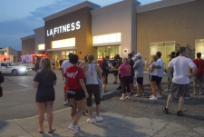 Patrons stand in the parking lot outside of LA Fitness in Bridgeville, Pa. after a reported shooting at the health club on Tuesday, Aug. 4, 2009. (AP / Tribune-Review, Joe Appel)