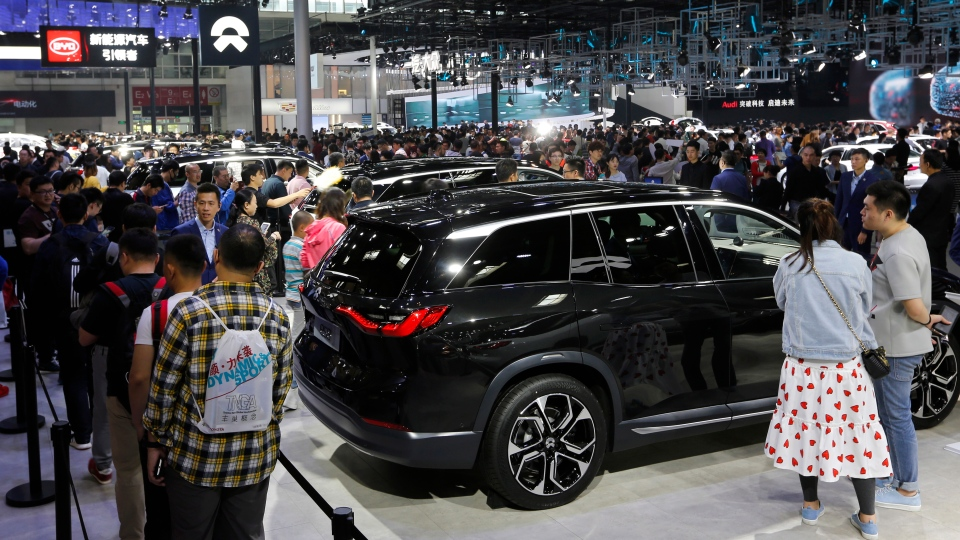 In this April 29, 2018, file photo, visitors watch an electric-powered SUV manufactured by Chinese automaker NIO during the China Auto Show in Beijing. (AP Photo/Andy Wong, File)