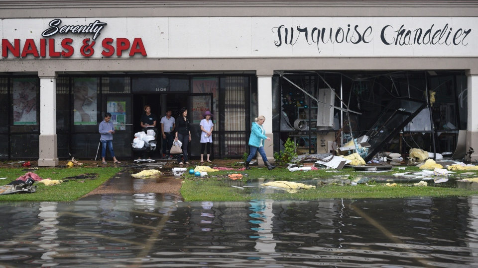 Shop owners and workers stand outside of their shops and walk amongst debris in the Pemberton Quarters strip mall following severe weather Saturday, April 13, 2019 in Vicksburg, Miss. (Courtland Wells/The Vicksburg Post via AP)