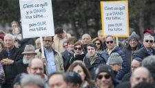 People hold up signs during a demonstration opposing the Quebec government's newly tabled Bill 21 in Montreal, Sunday, April 14, 2019. THE CANADIAN PRESS/Graham Hughes