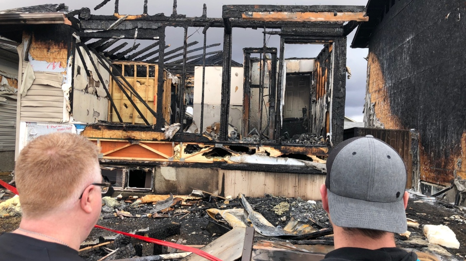 Neighbours look on after a house fire ripped through a Martensville home.