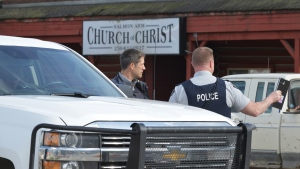RCMP officers talk behind a barricade in front of the Salmon Arm Church of Christ in Salmon Arm, B.C. on Sunday, April 14, 2019.THE CANADIAN PRESS/Murray Mitchell
