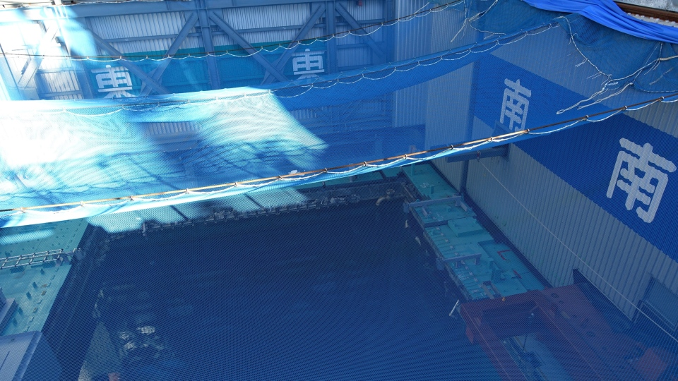 FILE - In this Jan. 25, 2018, file photo, a cooling pool where a total of mostly used 566 sets of fuel rods are stored underwater and covered by a protective net, waits to be removed in a step to empty the pool at Unit 3 of the Fukushima Dai-ichi nuclear power plant ahead of a fuel removal from its storage pool in Okuma, Fukushima Prefecture, northeast Japan. (AP Photo/Mari Yamaguchi, File)