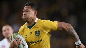 In this June 25, 2016, photo, Australian rugby union player Israel Folau, wearing tape on his wrist adorned with a cross, runs toward the try line to score against England during their rugby union test match in Sydney. (AP Photo/Rick Rycroft)