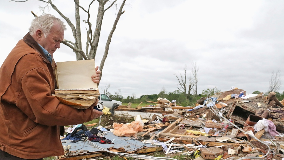 Robert Scott looks through a family bible that he just pulled out of the rubble Sunday, April 14, 2019, from his Seely Drive home outside of Hamilton, Miss. after an apparent tornado touched down. (AP / Jim Lytle)
