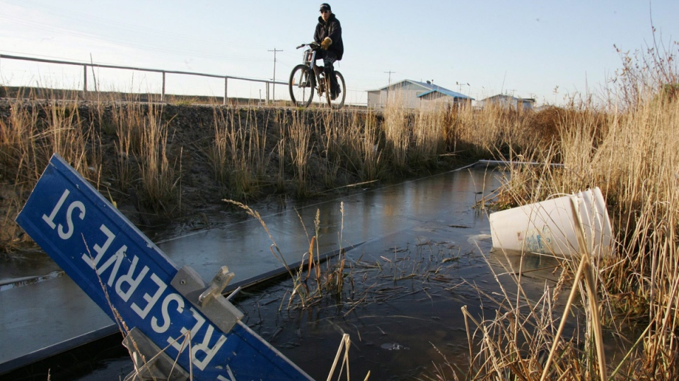 In this Oct. 28, 2005 file photo, Kenny Wynne rides his bike along a road on the Kashechewan native reserve in northern Ontario. (Jonathan Hayward / THE CANADIAN PRESS)