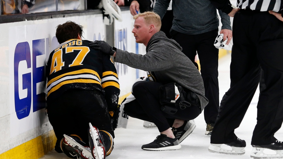 Personnel attend to Boston Bruins defenseman Torey Krug (47) as he needs help off the ice after taking a hit during the second period of Game 2 of an NHL hockey first-round playoff series against the Toronto Maple Leafs, Saturday, April 13, 2019, in Boston. (AP Photo/Mary Schwalm)