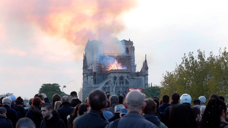People watch as flames and smoke rise from Notre Dame cathedral as it burns in Paris, Monday, April 15, 2019. (AP Photo/Thibault Camus)