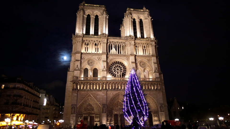 A Christmas tree is illuminated in front of Notre Dame Cathedral, in Paris, France, Thursday, Nov. 30, 2017. (AP Photo/Christophe Ena)
