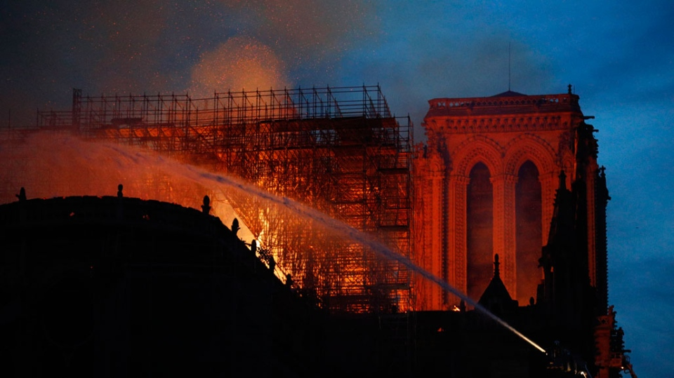 Firefighters use hoses as Notre Dame cathedral burns in Paris, Monday, April 15, 2019. (AP Photo/Francois Mori)