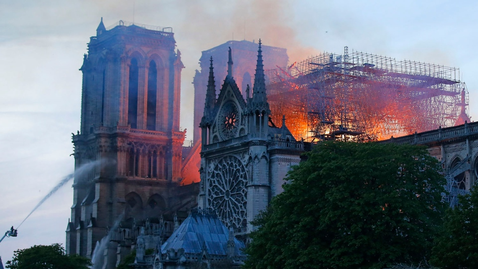 A firefighter tackles the blaze as flames and smoke rise from Notre Dame cathedral as it burns in Paris, Monday, April 15, 2019. (AP Photo/Michel Euler)