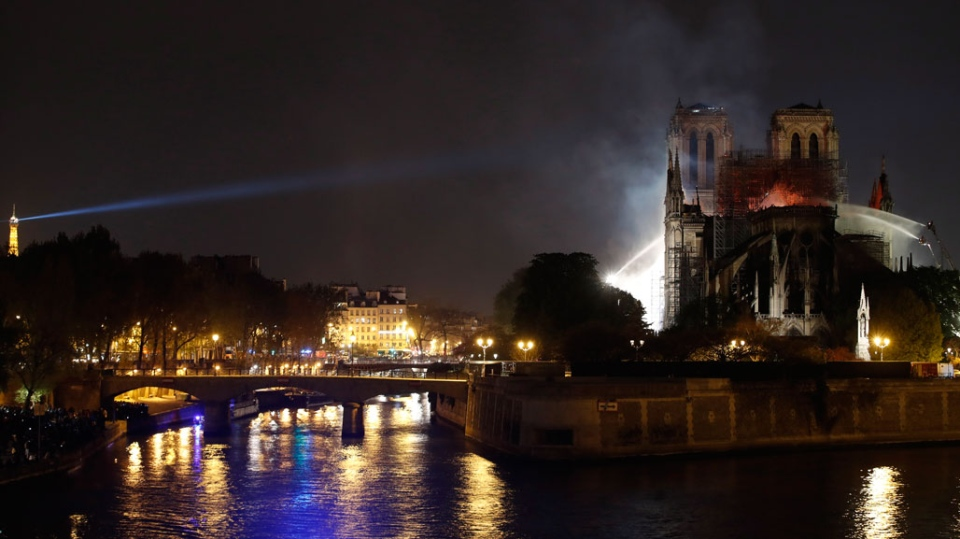 The Eiffel Tower, left, is seen while Notre Dame cathedral is burning in Paris, Monday, April 15, 2019. A catastrophic fire engulfed the upper reaches of Paris' soaring Notre Dame Cathedral as it was undergoing renovations Monday, threatening one of the greatest architectural treasures of the Western world as tourists and Parisians looked on aghast from the streets below. (AP Photo/Christophe Ena)