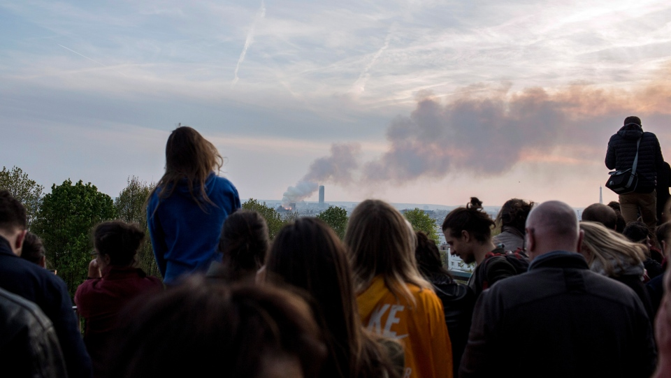 People watch Notre Dame cathedral burning in Paris, Monday, April 15, 2019. (AP Photo/Rafael Yaghobzadeh)