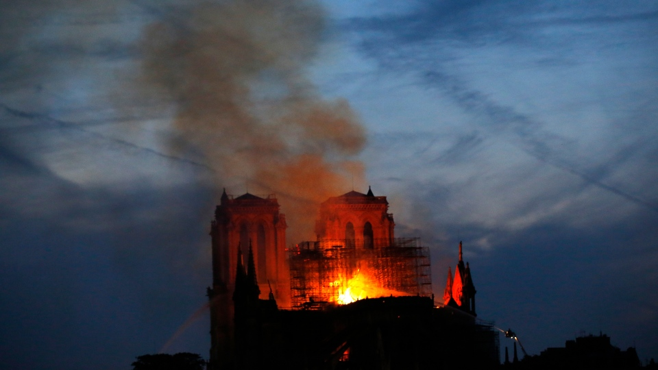 Firefighters tackle the blaze as flames and smoke rise from Notre Dame cathedral as it burns in Paris, Monday, April 15, 2019. (AP Photo/Michel Euler)