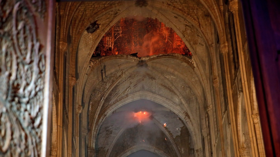 Flames and smoke are seen as the interior at Notre Dame cathedral in Paris, Monday, April 15, 2019. (Philippe Wojazer/Pool via AP)
