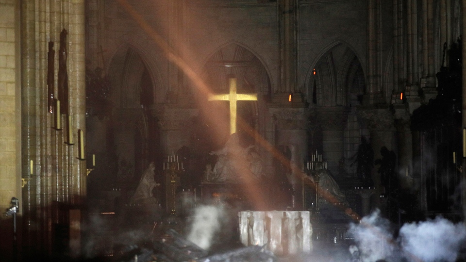 Smoke is seen around the altar inside Notre Dame cathedral in Paris, Monday, April 15, 2019. (Philippe Wojazer/Pool via AP)