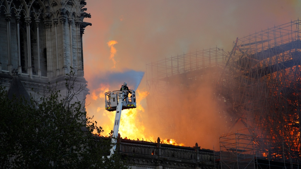 A firefighter uses a hose as Notre Dame cathedral burns in Paris, Monday, April 15, 2019. (AP Photo/Francois Mori)