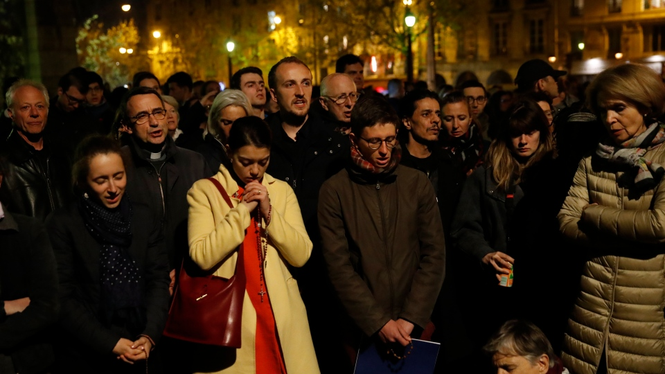 People pray as Notre Dame cathedral is burning in Paris, Monday, April 15, 2019. (AP Photo/Christophe Ena)