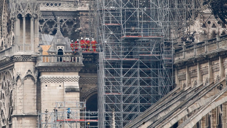 Firemen inspect the Notre Dame cathedral after the fire in Paris, Tuesday, April 16, 2019. (AP Photo/Christophe Ena)