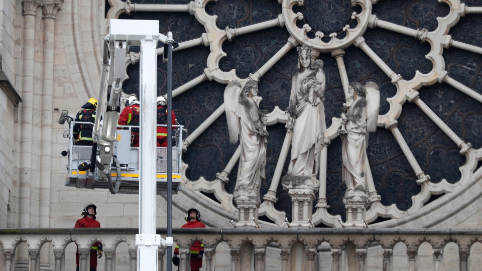 Firefighters work near the rose window of Notre Dame cathedral Tuesday April 16, 2019 in Paris. (AP Photo/Thibault Camus)