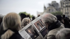 People gather near the damaged cathedral in Paris