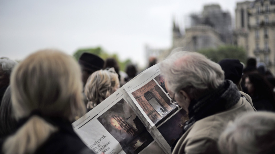 A man looks at pictures of the burning Notre Dame cathedral in a newspaper as he and others gather near the damaged cathedral in Paris, on April 16, 2019.  (Kamil Zihnioglu / AP)