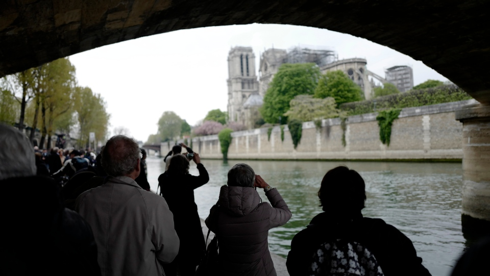 People take pictures of the damaged Notre Dame cathedral, rear, from the banks of Seine river after the fire in Paris, Tuesday, April 16, 2019. (AP Photo/Kamil Zihnioglu)