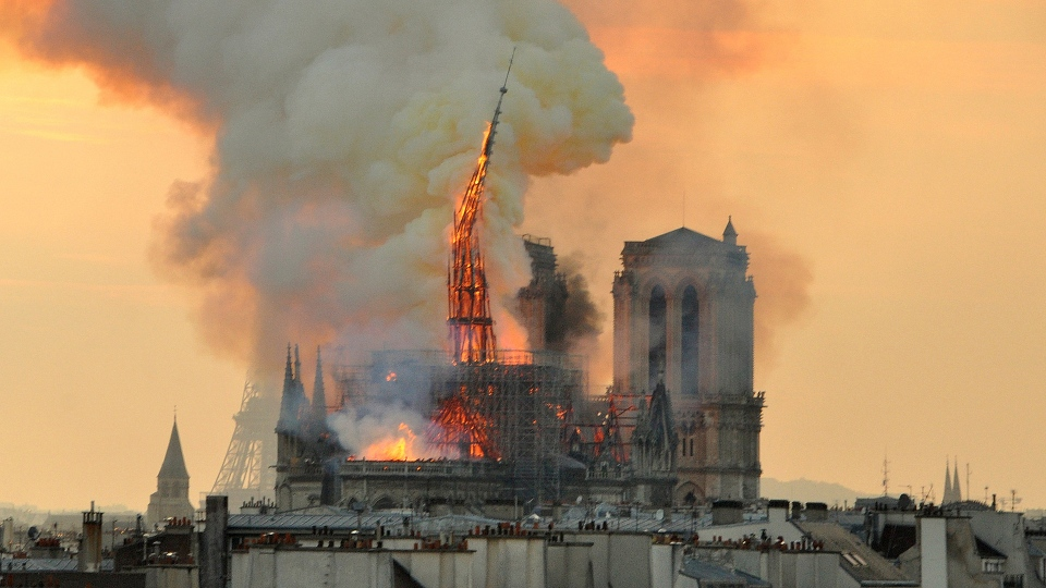 Flames and smoke rise from the blaze as the spire starts to topple on Notre Dame Cathedral in Paris, Monday, April 15, 2019. (AP / Thierry Mallet)