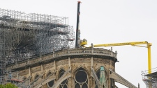 Experts prepare to remove a statue from Notre Dame