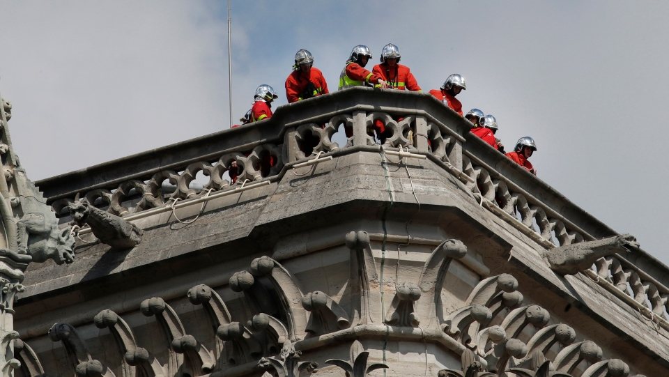 Firefighters inspect damage from the balcony of the Notre Dame cathedral, in Paris, Wednesday, April 17, 2019. (AP Photo/Christophe Ena)