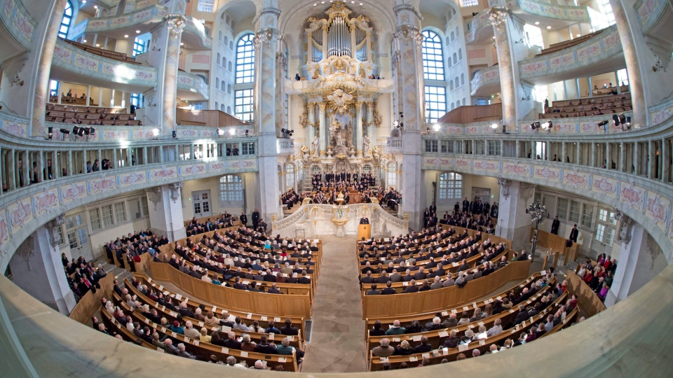 In this photo taken with a fisheye lens people sit on their places during a memorial service at the Frauenkirche cathedral in Dresden, eastern Germany, Friday, Feb. 13, 2015. (AP Photo/Jens Meyer)