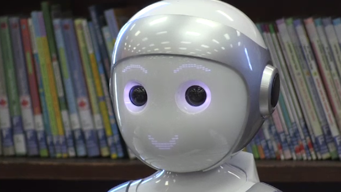 A photo of a smiling robot in a library
