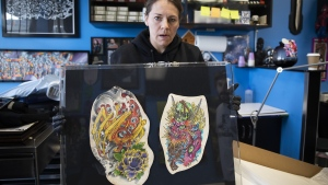 Cheryl Wenzel unboxes her late husband Chris Wenzel's preserved skin which displays his back, arm and thigh tattoos at Electric Underground Tattoos in Saskatoon, Tuesday, April 16, 2019. THE CANADIAN PRESS/Kayle Neis