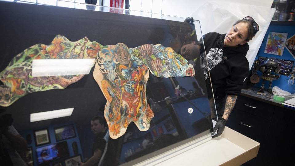 Cheryl Wenzel unboxes her late husband Chris Wenzel's preserved skin which displays his back, arm and thigh tattoos at Electric Underground Tattoos in Saskatoon, Tuesday, April, 16, 2019. THE CANADIAN PRESS/Kayle Neis
