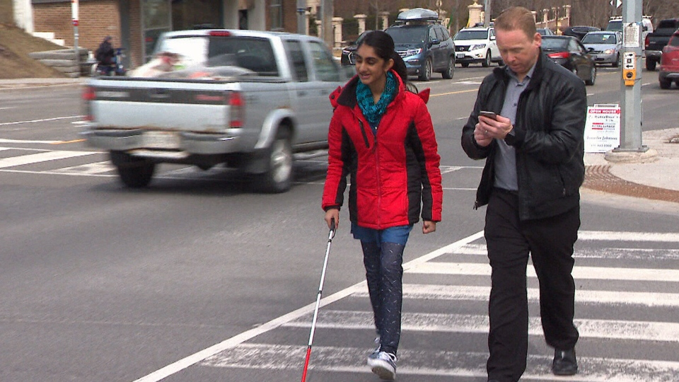 Mehak Aziz crosses a street in Toronto, with the help of a navigation tool on the smartphone she received through the 'Phone it Forward' campaign.