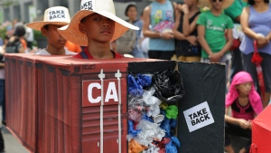 Filipino environmental activists wear a mock container vans filled with garbage to symbolize the 50 containers of waste that were shipped from Canada to the Philippines two years ago, as they hold a protest outside the Canadian embassy at the financial district of Makati, south of Manila, Philippines on Thursday, May 7, 2015. THE CANADIAN PRESS/AP, Aaron Favila