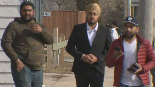 Gurjant Singh, middle, wears a black suit walking into Portage la Prairie courthouse ahead of Wednesday's sentencing. (Source: Josh Crabb/CTV News)