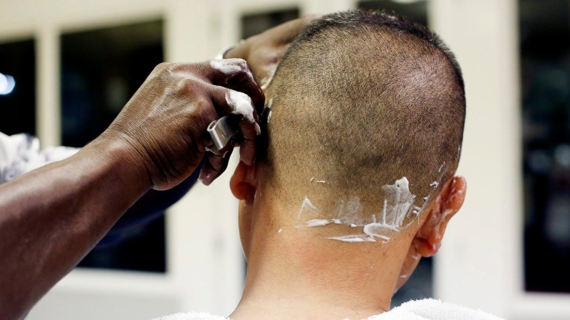 A barber cuts a customer's hair in this Feb. 27, 2015 photo in Marion, S.C. (AP Photo/The Morning News, Veasey Conway)