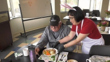Our Place community member Donny McLeod gets an Easter dinner from a volunteer Wednesday. (CTV Vancouver Island)