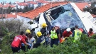 Rescue officials attend the scene after a tour bus crashed in Canico on Portugal's Madeira Island, Wednesday, April 17, 2019. The tour bus carrying German tourists crashed on Portugal's Madeira Island on Wednesday, killing more than a few dozen people and injuring a few dozen others, local authorities said. (Rui Silva/Aspress/Global Imagens via AP)