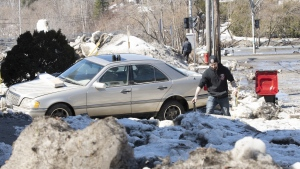 Resident Tommy Lechasseur cleans up near his car after the Chaudiere River flooded, Wednesday, April 17, 2019 in Beauceville, Que. Flooding forced the evacuation of 230 buildings and 36 people. THE CANADIAN PRESS/Jacques Boissinot