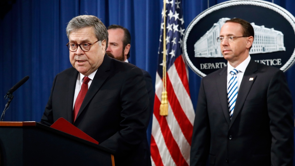 U.S. Attorney General William Barr speaks alongside Deputy Attorney General Rod Rosenstein, right, and Deputy Attorney General Ed O'Callaghan, rear left, about the release of a redacted version of special counsel Robert Mueller's report during a news conference, Thursday, April 18, 2019, at the Department of Justice in Washington. (AP Photo/Patrick Semansky)