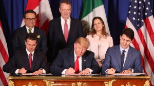 In this Nov. 30, 2018 file photo, President Donald Trump, center, sits between Canada's Prime Minister Justin Trudeau, right, and Mexico's President Enrique Pena Nieto as they sign a new United States-Mexico-Canada Agreement that is replacing the NAFTA trade deal. (AP Photo/Martin Mejia, File)